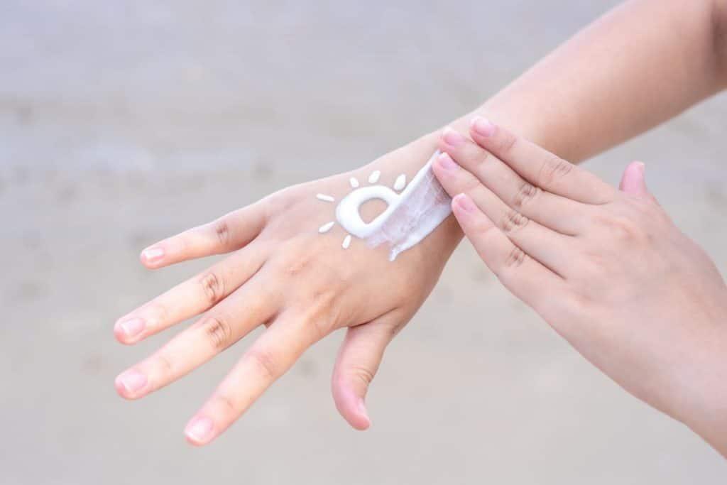 Les femmes asiatiques appliquent la protection solaire sur les mains et les bras