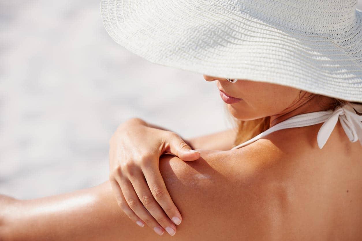 belle femme à la peau saine application de crème solaire à l'épaule