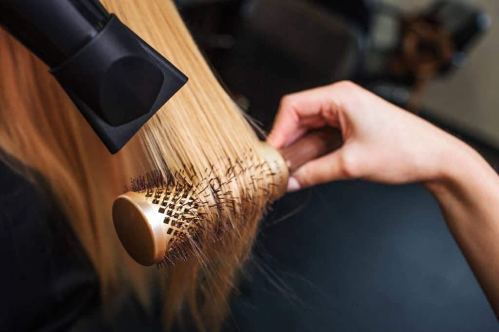 femme dans un salon de coiffure - séchage à la main cheveux blonds avec sèche-cheveux