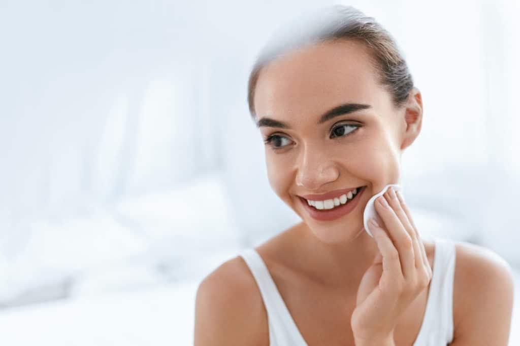 Fille nettoyant visage peau avec cosmétique