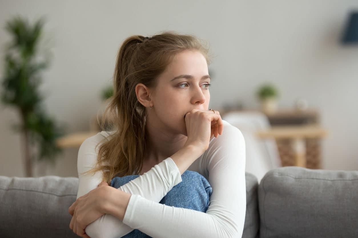 Femme inquiete assis sur le canapé seul à la maison