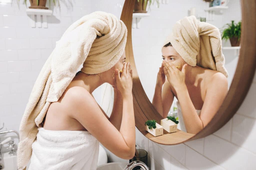 Jeune femme heureuse en serviette appliquant le gommage visage bio
