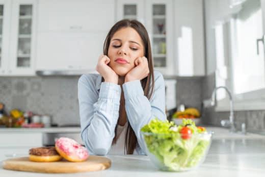 femme qui se sent mal devant de la nourriture