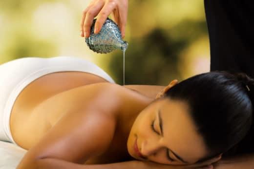 verser l'huile de massage ayurvedique sur le dos d'une femme